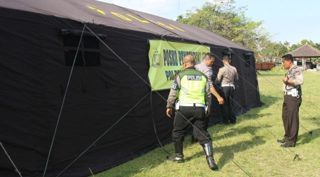 DIRIKAN TENDA: Anggota Polres Karangasem mendirikan tenda di lapangan Desa Rendang, Rabu (20/9).