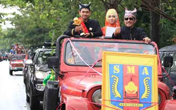 PEDULI LINGKUNGAN: Mujib memegang piala Adiwiyata Mandiri. Penghargaan Adiwiyata Mandiri SMAN 1 Giri dikirap keililing kota Banyuwangi, Jumat lalu (4/8).