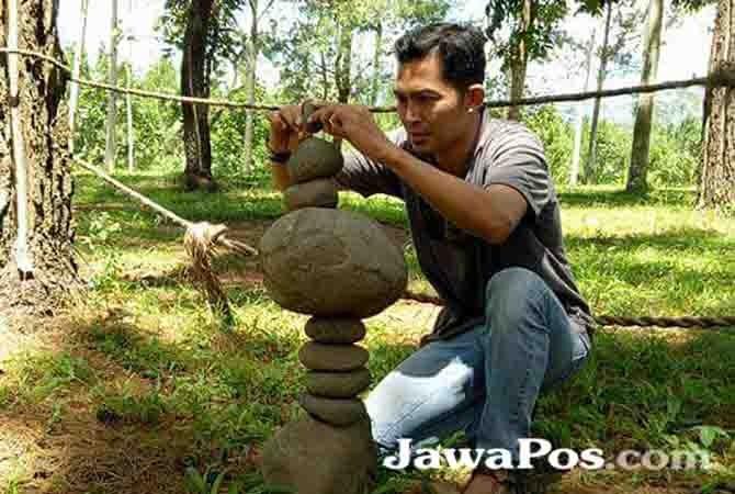 KESEIMBANGAN: Aji warga asal Genteng menetapkan batu di wisata Jambewangi, Kecamatan Sempu.