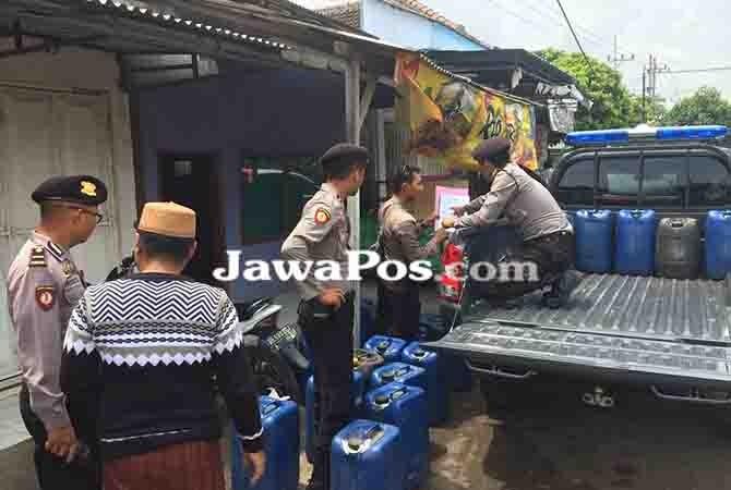 AKAN DIMUSNAHKAN: Anggota Sabhara Polres Banyuwangi menaikkan jeriken berisi arak yang disita dari rumah warga di Muncar.