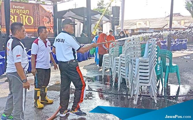 BERSIH-BERSIH: Kapolsek Gambiran AKP I Ketut Redana membantu membersihkan lokasi Festival Jaranan dengan menyemprot pakai air, kemarin (2/3).