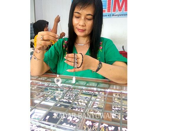 LOGAM MULIA: Salah seorang pedagang emas menunjukkan perhiasan emas hitam trend 2018 di Pasar Banyuwangi kemarin (11/3).