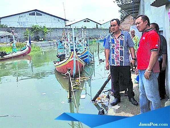 TKP: Kanitreskrim Polsek Muncar, Iptu Eko Darmawan (kiri) mendatangi lokasi tenggelamnya Kamal Wafa di sungai Kalimoro, Dusun Kalimoro, Desa Tembokrejo, Kecamatan Muncar, kemarin (21/3).