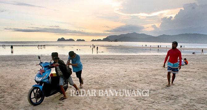 DITEGUR: Suyitno (kanan) menggiring dua remaja yang asyik main sepeda motor di Pantai Pulau Merah, kemarin (1/4).