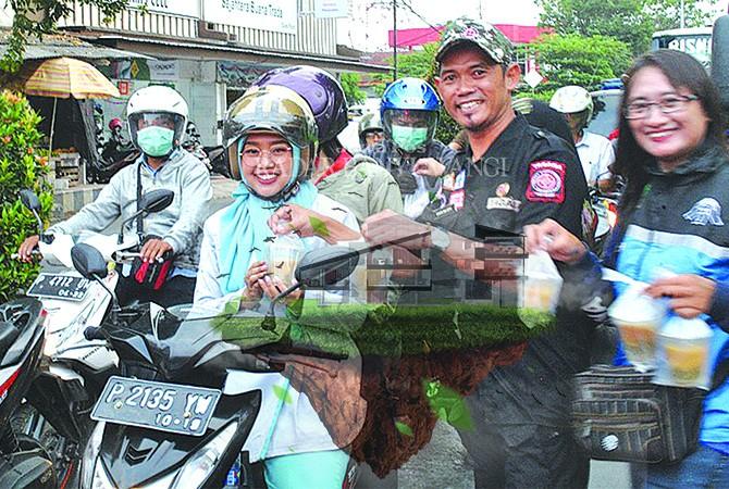 SEMANGAT: Anggota Tagana Banyuwangi membagikan takjil di jalan raya simpang tiga Desa Genteng Kulon, Kecamatan Genteng, Senin sore (4/6).