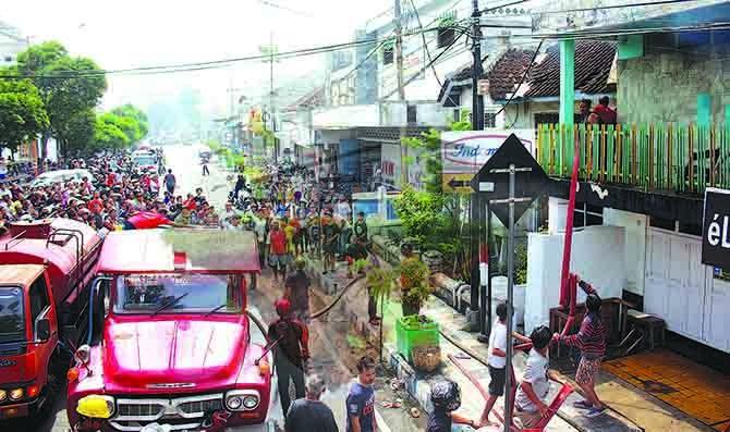 BERJUBEL DI JALAN: Warga menyaksikan terbakarnya ruko penyewaan Play Station yang berdekatan dengan titik nol KM Banyuwangi di Jalan PB Sudirman, kemarin.