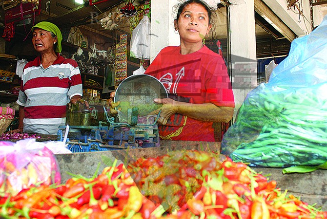 PILAH: Umi Khulsum menimbang bawang merah di Pasar Genteng II, Kecamatan Genteng, kemarin (2/7).