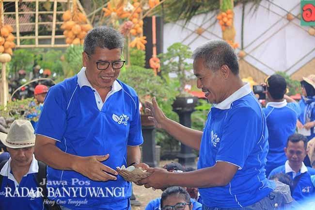 SELAMATAN: Kadisperta Banyuwangi Arief Setiawan menerima tumpeng dari Sekretaris Disperta Dewa Made Wicaksana saat soft launching BAE 2018 kemarin.
