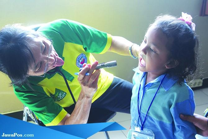 BUKA MULUT: Para penyuluh mengontrol kesehatan gigi anak.