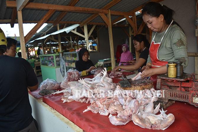 STOK MINIM: Ririn, salah satu pedagang di Pasar Mimbaan Baru, Panji memotong daging ayam yang dijualnya, kemarin.