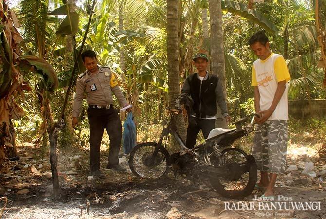 TINGGAL RANGKA: Anggota Polsek Rogojampi dibantu warga mengamankan sepeda motor milik Rahmawati yang dibakar massa di Desa Patoman, Blimbingsari, Rabu (31/10).
