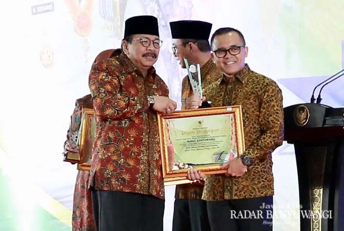 PENGHARGAAN: Bupati Anas menerima piagam penghargaan bidang pertanian dari Gubernur Soekarwo di Surabaya, Senin (5/11).