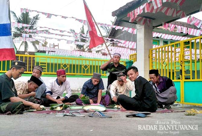 Warga Desa kelir menikmati sego golongan di pinggir jalan desa setempat kemarin (6/11)