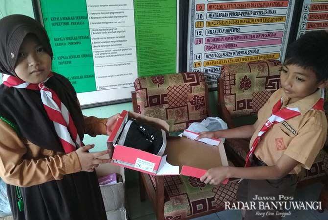 PEDULI: Alan Nurfahmi menerima bantuan sepatu dalam program SAS di SDN 1 Jambewangi.