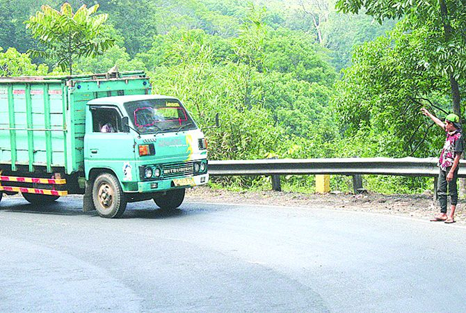 MENGATUR: Faisal Ardian Hidayat memberi arahan kepada pengguna jalan agar mengurangi laju kendaraannya di jalan raya Desa Kalibaru Manis, Kecamatan Kalibaru, kemarin (19/11).