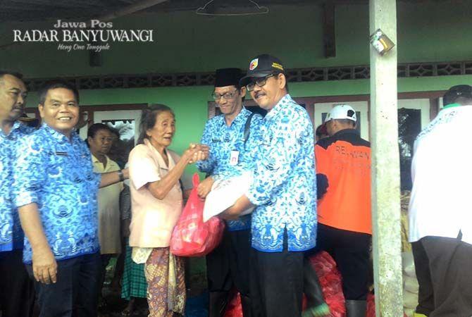 TANGGAP DARURAT: Kepala Pelaksana BPBD Fajar Suasana menyerahkan bantuan makanan kepada warga terdampak banjir di Petak 56 Dusun Ringinagung, Desa Pesanggaran