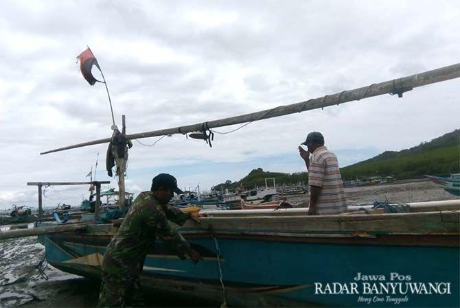 DIPERBAIKI: Ngatimin dibantu warga memperbaiki perahu speed di Pantai Grajagan, Desa Grajagan, Kecamatan Purwoharjo, Jumat (30/11).