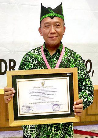 BANGGA: Sukirno dengan piagam penghargaan sekolahnya sebagai sekolah adiwiyata nasional dari Kementerian LH dan Kemendikbud RI.