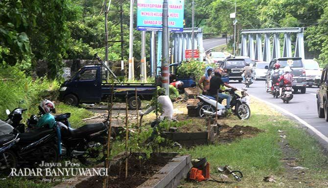 RIJIG-RIJIG: Warga membersihkan taman sisi barat Jembatan Tambong. Taman yang berada di atas jembatan lama ini diusulkan untuk difungsikan kembali.