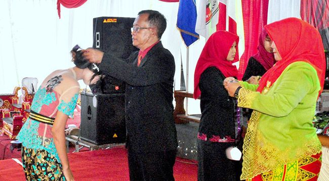 SIMBOLIS: Kepala SMK 17 Agustus 45 Cluring Bibit Kuswinarno mengenakan gordon dalam pelepasan siswa kelas XII di sekolahnya, Kamis (25/4).