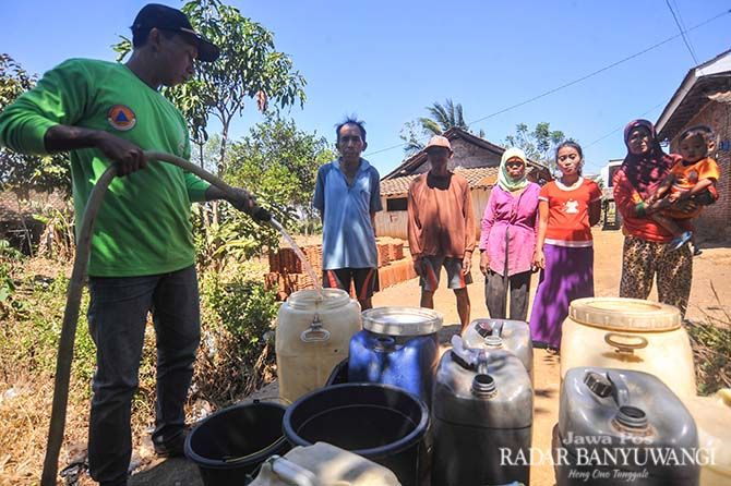 DAMPAK KEMARAU PANJANG: Warga Sidodadi, Kecamatan Wongsorejo antre mendapatkan air bersih. Setiap musim kemarau, sebagian warga di desa tersebut  butuh pasokan air bersih.