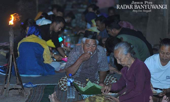 Masyarakat menikmati tumpeng sewu di acara adat Desa Kemiren, Glagah, Minggu (5/8) malam.