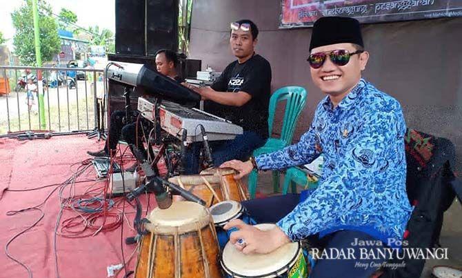 BERJIWA SENI: Anton Sujarwo yang masih mengenakan seragam dinas kades menabuh kendang dalam acara pernikahan di desanya.