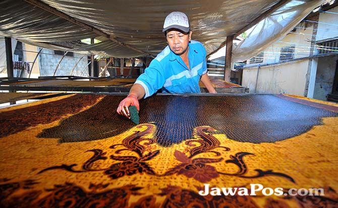 PROSES PEWARNAAN: Seorang pekerja sedang mewarnai batik di rumah batik Mbah Kulsum, Kelurahan Temenggungan, Banyuwangi, kemarin.