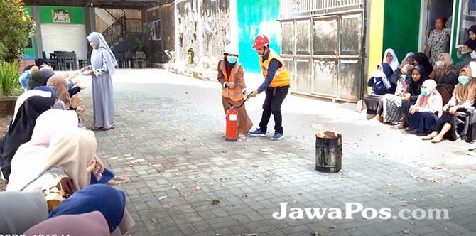 SIMULASI: Tim dosen Poliwangi memberikan edukasi dan simulasi menggunakan Alat Pemadam Api Ringan (APAR) di Ponpes Darussholah, Kecamatan Singojuruh, Banyuwangi.
