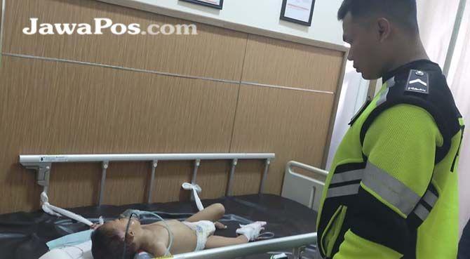 KRITIS: Anggota Lantas Polsek Kalibaru menjenguk korban Abdillah yang masih menjalani perawatan di RSu Bhakti Husada, Krikilan, kemairn (6/10).