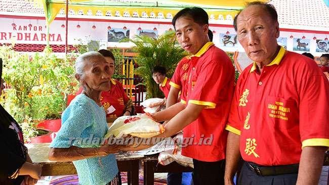 SANTUNAN : Ketua panitia acara Irwan Kuswanto (dua dari kanan) menyerahkan santunan pada warga kurang mampu yang ada di sekitar TITD Tik Liong Tian Rogojampi, Rabu (4/12).