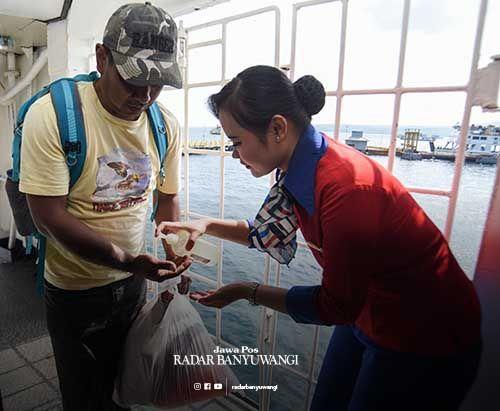 ANTISIPASI KORONA: Pramugari kapal memberikan hand sanitizer kepada penumpang kapal tujuan Ketapang-Gilimanuk, kemarin.