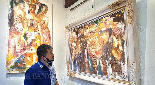 BERBURU LUKISAN: Ketua Kadin Banyuwangi David Wijaya Tjoek melihat lukisan barong bali karya S Yadi K di Jalan Widuri, Glagah kemarin sore.