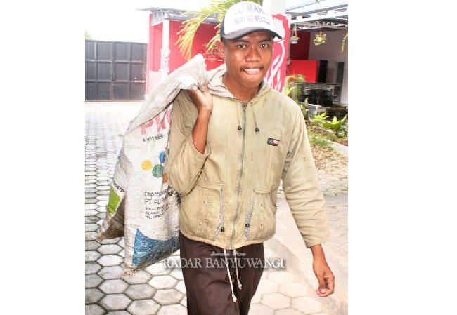 PANTANG MENYERAH: Donni Crismajaya keliling desa mencari botol bekas untuk dijual di Desa Yosomulyo, Kecamatan Gambiran, kemarin (22/4).