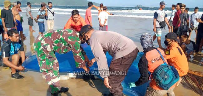 TAK BERNYAWA: Petugas mengevakuasi jenazah korban yang baru ditemukan di Pantai Mustika, Desa Sumberagung, Kecamatan Pesanggaran, kemarin (23/6).