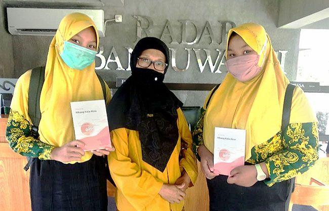 BERBAJU BATIK : Dua siswi SMPN 1 Kalipuro tidak mau ketinggalan untuk membuat Pentigraf.