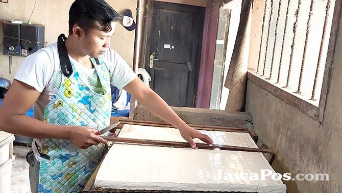 MENIPIS: Mulyadi memotong tahu menjadi lebih kecil agar bisa untung saat harga kedelai meroket di Desa Yosomulyo, Kecamatan gambiran, kemarin (10/1).