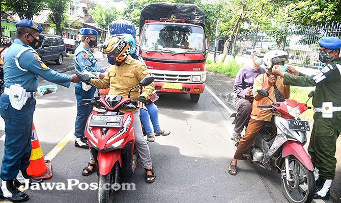 Anggota POMAL membagikan masker kepada pengguna jalan di sekitar Pelabuhan Ketapang.