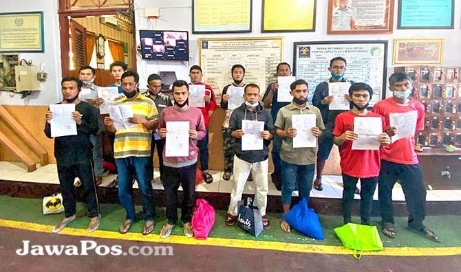 BISA PULANG: Belasan napi menunjukkan surat asimilasi saat hendak keluar Lapas Kelas IIA Banyuwangi, kemarin (21/2).