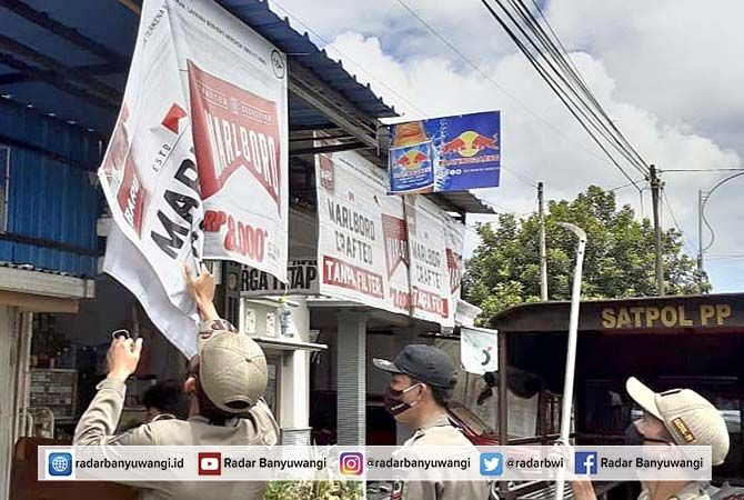 TURUNKAN: Petugas menurunkan spanduk iklan roko tidak berizin di Desa Genteng Kulon, Kecamatan Genteng, kemarin (6/4).