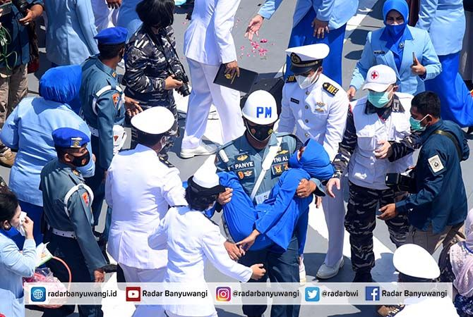 PINGSAN: Salah seorang keluarga awak KRI Nanggala-402 harus dibopong anggota TNI AL saat mengikuti upacara tabur bunga kemarin.