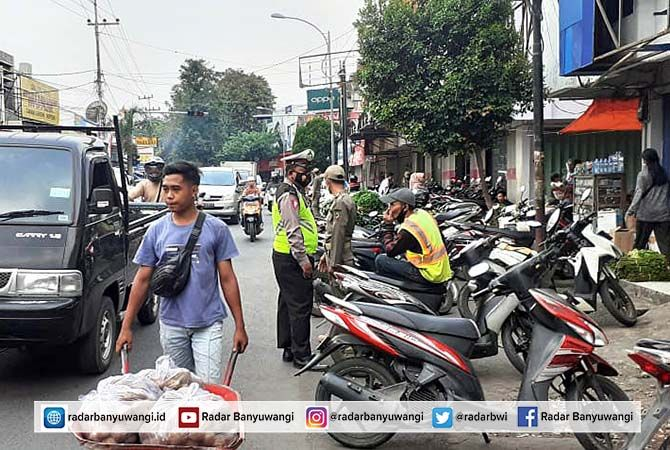 KENDALIKAN: Polisi dan Satpol PP mengatur parkir dan arus lalu lintas di Jalan Gajah Mada, Desa Genteng Kulon, Kecamatan Genteng, kemarin (30/4).