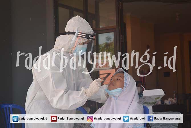 PENCEGAHAN: Petugas mengambil sampel liur untuk rapid antigen di teras Rusunawa, kompleks Pondok Pesantren Darusssalam, Blokagung, Desa Karangdoro, Kecamatan Tegalsari, kemarin (6/7)