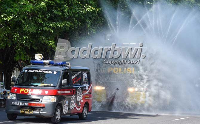 CEGAH PENYEBARAN COVID: Kendaraan taktis water cannon milik Polresta Banyuwangi menyemprotkan cairan disinfektan di jalan protokol dekat Simpang Lima Banyuwangi, kemarin.