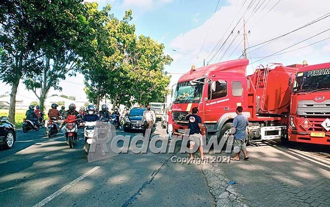 TAK ADA KORBAN: Unit lantas Polsek Rogojampi membantu mengevakuasi truk tangki yang melintang di Jalan Raya Kabat kemarin pagi (14/7).