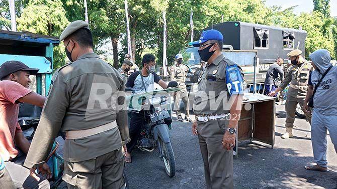 DITERTIBKAN: Personel Satpol PP Banyuwangi menertibkan para PKL di Jalan Veteran, Kepatihan, Banyuwangi. Sejumlah PKL terdampak PPKM Darurat mempertanyakan kompensasi penutupan.