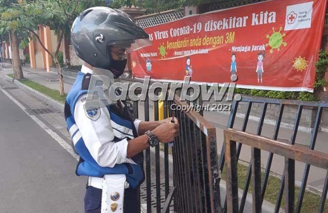 RESPONS CEPAT: Petugas Dinas Perhubungan Banyuwangi memasang stiker scot light pada pagar penyekatan di Jalan Adi Sucipto Banyuwangi kemarin (15/7).