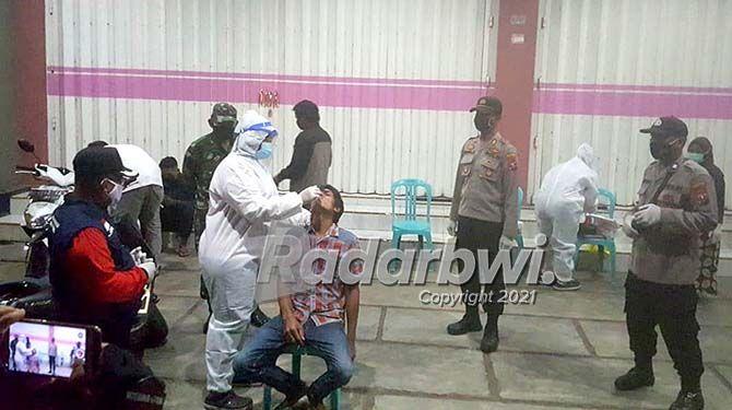 TEKAN PENYEBARAN: Petugas melakukan tes antigen di termpat pada remaja yang melanggar prokes di Desa/Kecamatan Purwoharjo pada Rabu malam (22/7).