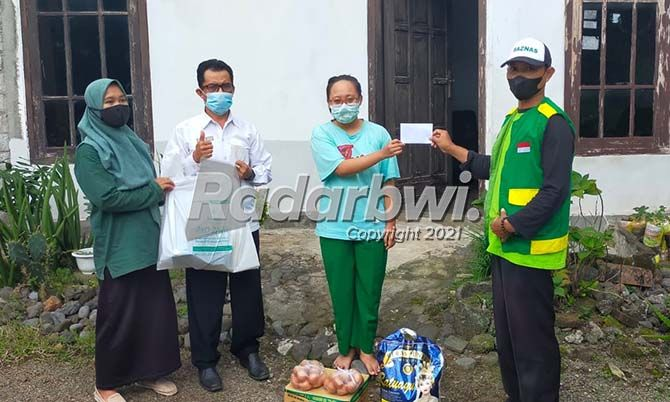 BANTU WARGA KESUSAHAN: Baznas Banyuwangi melalui Koordinator Wilayah Genteng, Anang Ma'ruf Masyhuri saat menyerahkan bantuan dari muzakki ke Syahrul Munir.