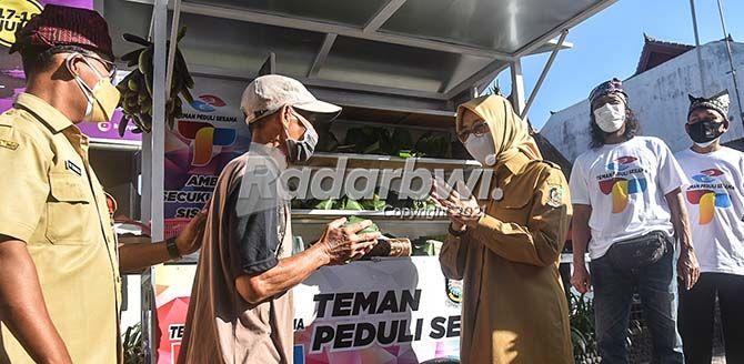 EMPATI UN TUK SESAMA: Bupati Ipuk Fiestiandani memberikan nasi bungkus kepada warga di lapak berbagi Teman Peduli Sesama (TPS) depan kantor Disbudpar Banyuwangi, kemarin.